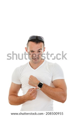 nervous handsome man in white t-shirt pointing a finger at clock to camera with raised one eyebrow - stock photo