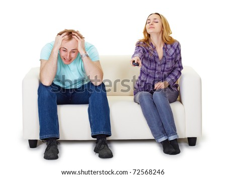 Nervous husband and wife sitting on the couch watching TV isolated on white background - stock photo