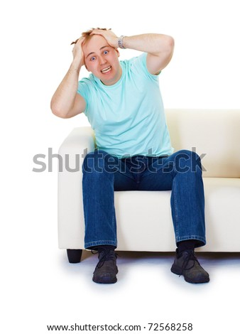 Nervous hysteria man sitting at home on the couch isolated on white background - stock photo