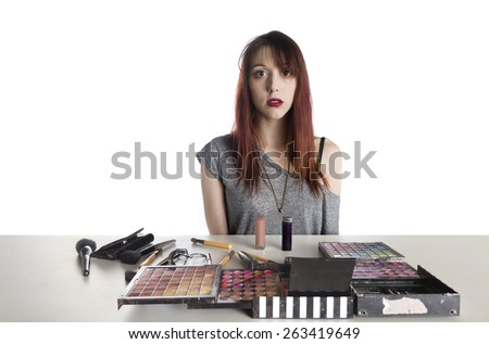 Nervous Looking Young Woman with Large Palette of Make Up and Brushes Spread Out in front of Her - stock photo