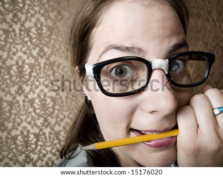 Nervous nerdy Woman Chewing on a Yellow Pencil - stock photo