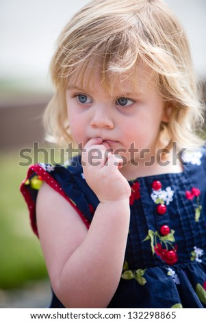 nervous toddler girl biting her lip as she thinks - stock photo