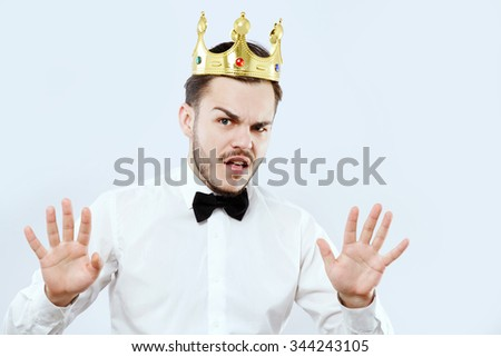 Nervous young man, with beard and mustaches, wearing in white shirt, bow and gold crown, posing like he said calm down, on white background and saying something, in studio, waist up - stock photo