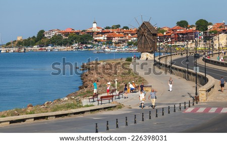 Nesebar, Bulgaria - July 21, 2014: Coastal landscape with road and old windmill, Black Sea coast in sunny day. Tourists walk on the street