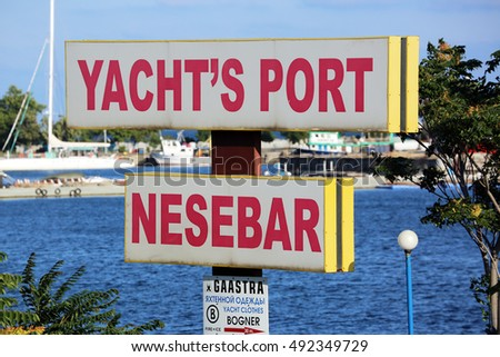 Nessebar, Bulgaria - July 16, 2016: Yacht's Port Of Nessebar Sign On A Pole in Nessebar. Bulgarian Black Sea Coast On The Background