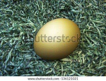 Nest Egg; a single golden egg laid upon a soft, secure nest of shredded paper currency. - stock photo