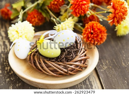 Nest with Easter Eggs and Flowers in the Background - stock photo