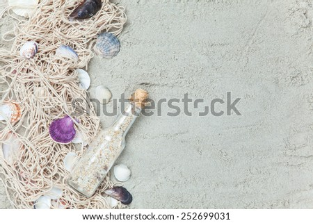 Net and shells with bottle on sand background. - stock photo