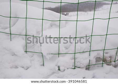 net fence covered by snow  - stock photo