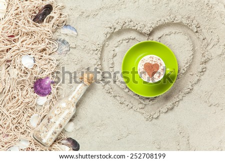 Net, shells with bottle and gift box with cup heart shape on sand background. - stock photo
