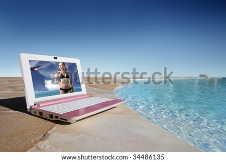 netbook near to swimming pool - stock photo