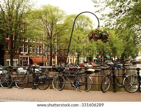 NETHERLANDS. AMSTERDAM - JUNE 23, 2015: Bicycle parking on the quay of the channel on the background of the historic architecture summer  day. - stock photo