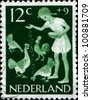 NETHERLANDS - CIRCA 1962: A stamp printed in Netherlands honoring Child Welfare, shows girl feeding chickens, circa 1962 - stock photo