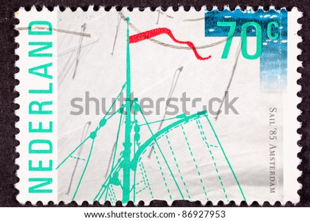 "NETHERLANDS - CIRCA 1985:  A stamp printed in the Netherlands commemorates ""Sail '85 Amsterdam"" and shows top of a ships mast against a canvas sail background, circa 1985."