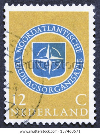 NETHERLANDS - CIRCA 1959: a stamp printed in the Netherlands shows NATO Emblem, 10th Anniversary of NATO, circa 1959   - stock photo