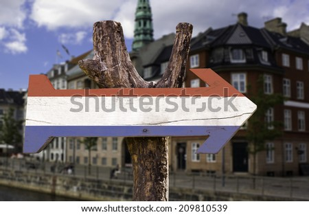 Netherlands wooden sign with a city background - stock photo