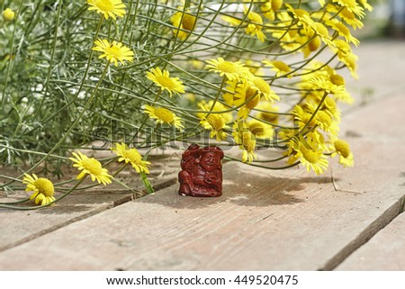 Netsuke worker with hammer in shadow of yellow flowers - stock photo