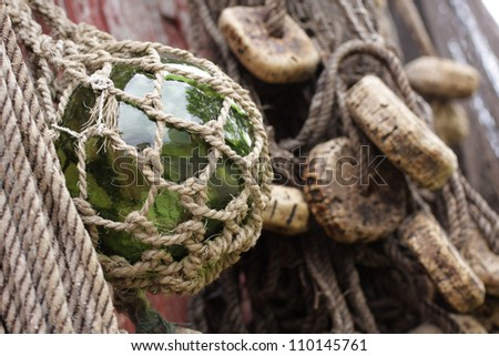 Netted green glass float hanging at a boathouse wall. Closeup photo taken at Norwegian coast. - stock photo