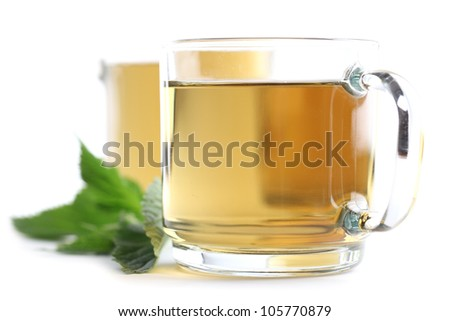 Nettle and freshly made nettle tea in glass cups isolated on white background. Shallow dof