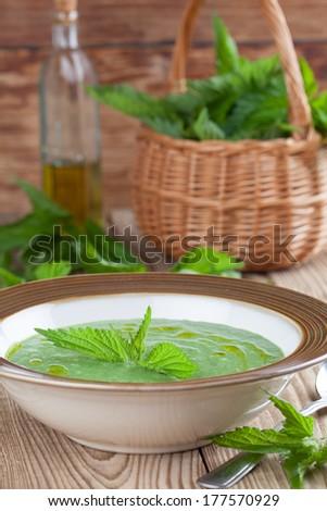 Nettle cream soup on wooden background. Shallow dof - stock photo