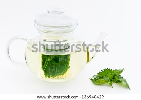 Nettle infusion in glass teapot with fresh nettle leaves - stock photo