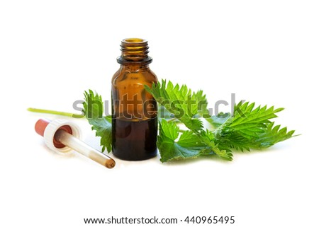 nettle tincture in a small bottle and fresh leaves isolated with shadows on a white background, medicinal herb for overweight, diabetes and kidney weakness, selected focus, narrow depth of field - stock photo
