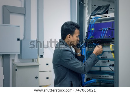 Network administrator talking on the ip phone and connecting utp cable to the network switch in datacenter room