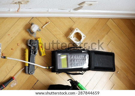 Network and spectrum analyzers and other tools on wooden parquet floor next tot electrical and antenna wall sockets just after installation of digital fiber optic cable for high speed internet - stock photo