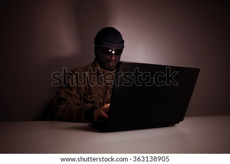 Network criminal man examining a laptop computer. The man has a camouflage jacket, sunglasses and balaclava. The photo is underexposed. Image includes a vintage effect.