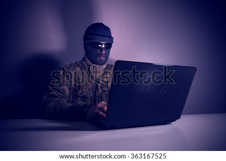 Network criminal man examining a laptop Computer. The man has a camouflage jacket, sunglasses, and balaclava. The photo is underexposed. Image includes a effect.  - stock photo