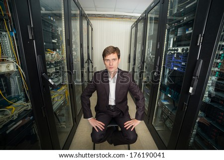 Network Engineer in the server room in a suit sitting on a chair, distorted perspective