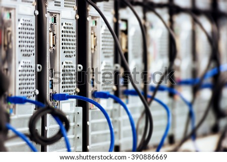 Network LAN cables in the back of servers in a data center background IT - stock photo