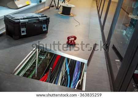 Network wires in the floor, which can be seen through the open hatch. Undergoing renovations. It should be a tool box. - stock photo