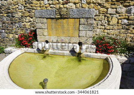 NEUCHATEL, SWITZERLAND - SEPTEMBER 09, 2015: Small fountain at the old walls probably reminds former the castle moat in the city with a population of approx. 34000 mainly French-speaking citizens - stock photo