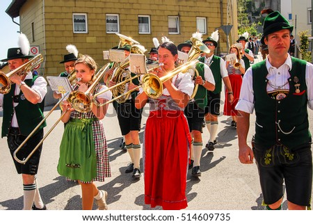 Neuoetting,Germany-May 1,2012:Brass band in typical bavarian clothes arrives at the scene of a Maypole setting.