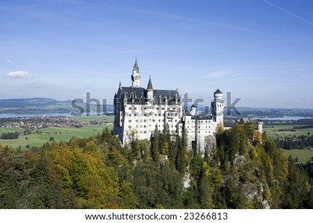 Neuschwanstein castle in autumn on a clear sunny day with lake and city visible, Bavaria Germany - stock photo