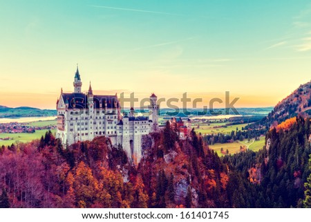Neuschwanstein, Lovely Vintage Blue Yellow Autumn Landscape Panorama Picture of the fairy tale castle near Munich in Bavaria, Germany with colorful trees in the morning hours - stock photo