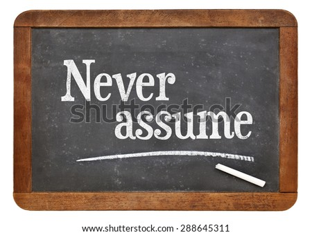 Never Assume Advice   Text In White Chalk On A Vintage Slate Blackboard