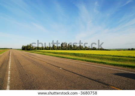 never ending highway through green fields and blue cloudy sky - stock photo