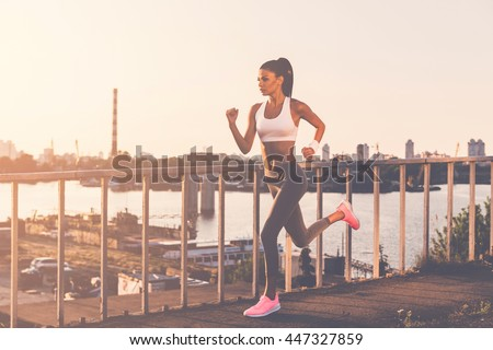 Never give up and keep moving! Full length of beautiful young woman in sports clothing running along the bridge  - stock photo