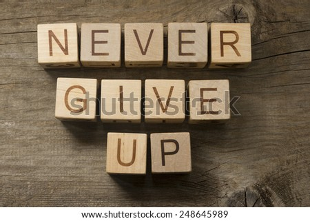 Never give up text on a wooden background - stock photo