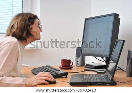 Never old enough - senior woman with computer - stock photo