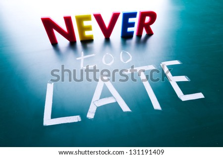 Never too late concept, words on blackboard