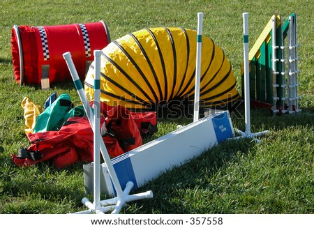 New agilitiy equipment used in timed runs of an obstacle course.  Dogs are grouped by sizes and race for  fastest time and fewest faults   Pictured: shoot, tunnel, winged jumps,  broad jump. - stock photo
