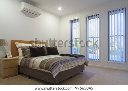New, air conditioned bedroom with double bed, pillows and covers. - stock photo