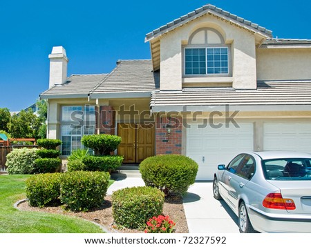 New American dream home with a beautiful blue sky in background and brand new car parked outside. - stock photo