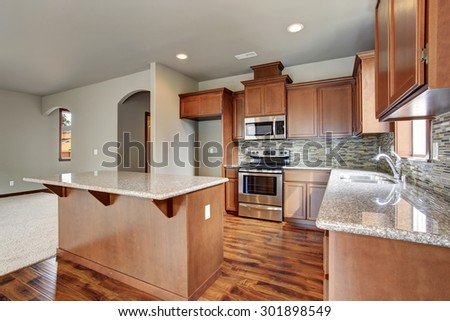 New 2015 American middle class kitchen. Cherry wood color of cabinets and laminate flooring.