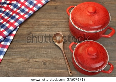 New And Clean Two Covered Red Saucepan, Wooden Spoon And Checkered Tablecloth On The Rough Rustic Brown Wood Table Background, Top View, - stock photo
