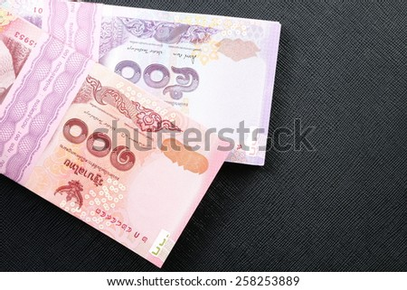 New and latest edition of Thailand one hundred and five hundred baht banknotes put on the black color leather background represent the Thai financial and monetary related. - stock photo