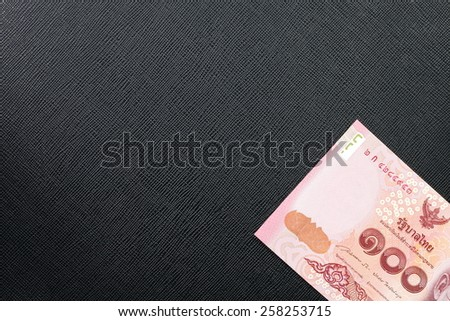 New and latest edition of Thailand one hundred baht banknotes put on the black color leather background represent the Thai financial and monetary related. - stock photo